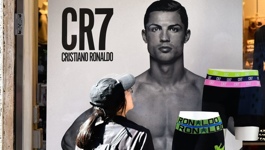 A passerby watches an advertising poster for an underwear brand, showing a picture of Juventus' Portuguese forward Cristiano Ronaldo in a shop window, on October 9, 2018 in downtown Rome. - Cristiano Ronaldo faces rape allegations after US police on October 1, 2018 re-opened an investigation into claims by former American model Kathryn Mayorga that the five-time Ballon d'Or winner raped her in a Las Vegas hotel in June 2009. (Photo by Alberto PIZZOLI / AFP)        (Photo credit should read ALBERTO PIZZOLI/AFP/Getty Images)