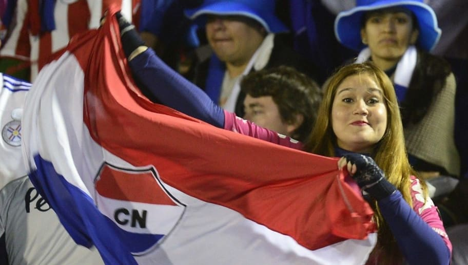 A Paraguayan fan waves a Nacional team flag as she waits for the start of the Copa Libertadores semifinal second leg football match between Uruguay's Defensor and Paraguay's Nacional, at Centenario Stadium in Montevideo on July 29, 2014.  AFP PHOTO / PABLO PORCIUNCULA        (Photo credit should read PABLO PORCIUNCULA/AFP/Getty Images)