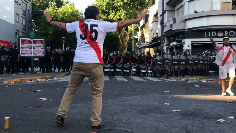 Video grab showing a supporter of River Plate gesturing at riot police in the surroundings of the Monumental stadium in Buenos Aires following an attack on the Boca team bus before the all-Argentine Copa Libertadores second leg final match between River Plate and Boca Juniors on November 24, 2018. - Saturday's 'superclasico' Copa Libertadores final was postponed until Sunday following an attack on the Boca team bus that left players affected by smoke inhalation and broken glass. (Photo by Ivan PISARENKO / AFP)        (Photo credit should read IVAN PISARENKO/AFP/Getty Images)