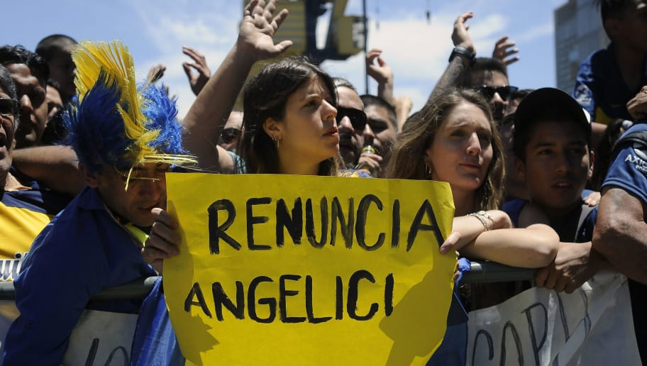 A Boca Juniors' supporter holds a sign demanding the resignation of the team's president Daniel Angelici, as they wait for their team players outside their hotel in Buenos Aires, after the all-Argentine Copa Libertadores second leg final match against River Plate was postponed on November 25, 2018. - The second leg of the Copa Libertadores final has been postponed for the second time in as many days following an attack on the Boca Juniors team bus by River Plate fans, Conmebol said Sunday. (Photo by JAVIER GONZALEZ TOLEDO / AFP)        (Photo credit should read JAVIER GONZALEZ TOLEDO/AFP/Getty Images)