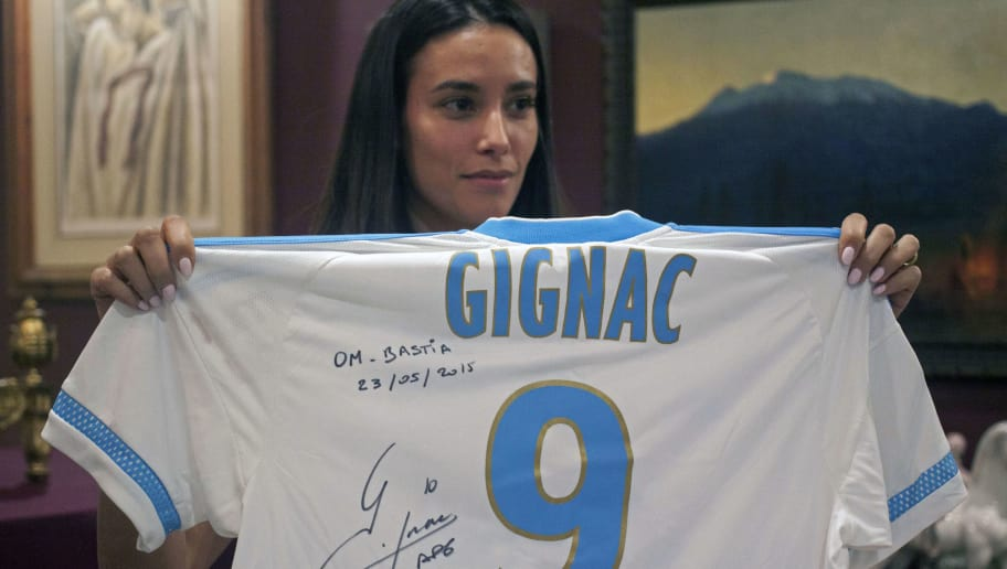 Deborah Gignac, wife of French footballer Andre Pierre Gignac shows his husband's Marseille autographed jersey, the last team he played for before coming to Mexicos's Tigres from France, to be auctioned in Monterrey Nuevo Leon, Mexico on September 12, 2017. Gignac is organising a charity auction to be held on September 27, with at least 120 articles donated by different athletes, such as Lionel Messi, Cristiano Ronaldo and Argentine and Mexican national team players. The profits will support the treatment for six-year-old Zoe, who suffers from a brain tumour.  / AFP PHOTO / Julio Cesar AGUILAR        (Photo credit should read JULIO CESAR AGUILAR/AFP/Getty Images)