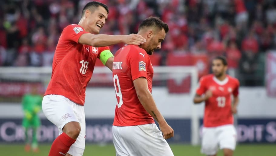 Switzerland's forward Haris Seferovic (C) reacts with teammate Switzerland's midfielder Granit Xhaka (L) after scoring his team's fifth goal during the UEFA Nations League group stage, league A, group 2 football match between Switzerland and Iceland at the Kybunpark stadium in St- Gallen on September 8, 2018. (Photo by Fabrice COFFRINI / AFP)        (Photo credit should read FABRICE COFFRINI/AFP/Getty Images)