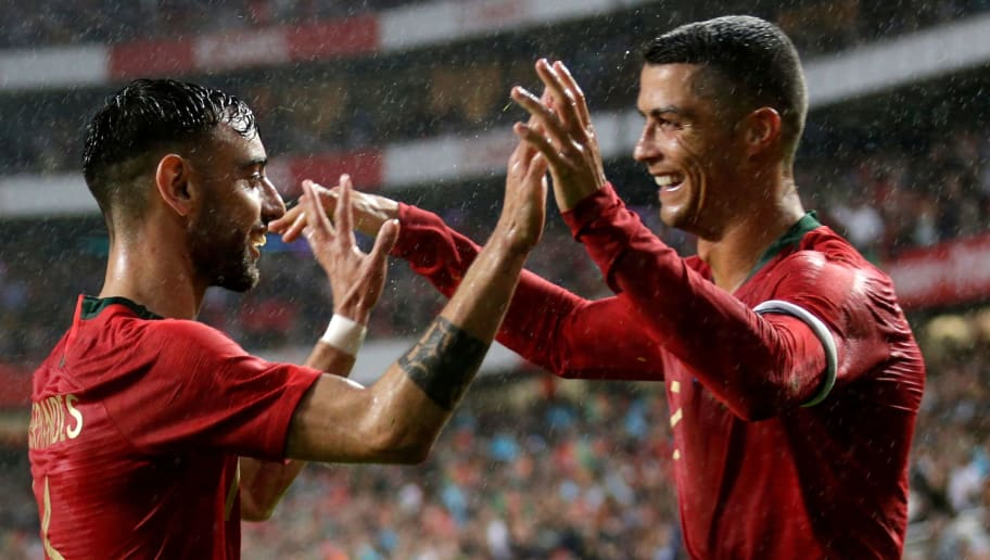 Portuguese defender Bruno Fernandes (L) celebrates with captain Cristiano Ronaldo after scoring a goal during the friendly football match between Portugal and Algeria, on June 7, 2018 at the Luz stadium  in Lisbon. (Photo by JOSE MANUEL RIBEIRO / AFP)        (Photo credit should read JOSE MANUEL RIBEIRO/AFP/Getty Images)