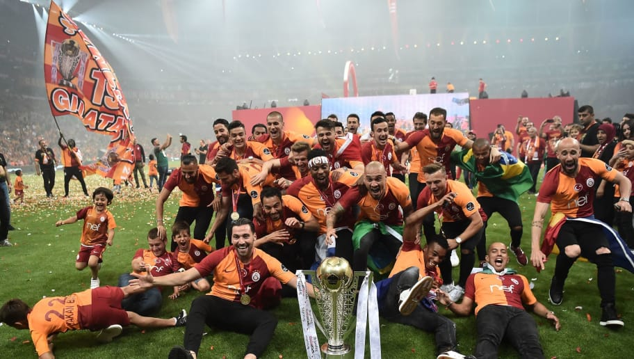 Galatasaray's players celebrate their 2017-2018 Turkish league champion title during a trophy cerenomy a day after the Turkish Spor Toto Super league football match between Goztepe and Galatasaray at the TT Arena stadium on May 20, 2018 in Istanbul. (Photo by OZAN KOSE / AFP)        (Photo credit should read OZAN KOSE/AFP/Getty Images)