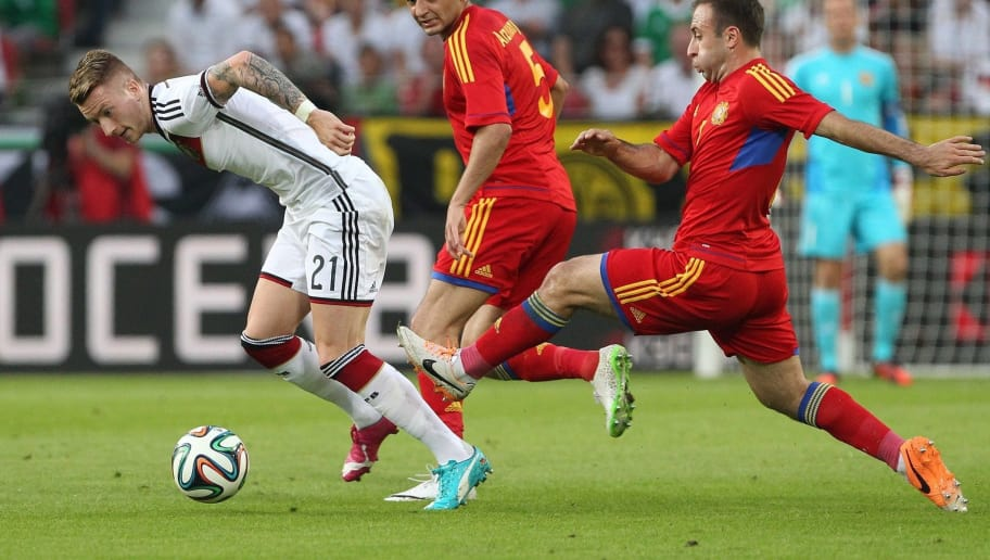 Germany's midfielder Marco Reus (L), Armenia's defender Robert Arzumanyan (C) and Armenia's midfielder Artur Yedigaryan vie for the ball during the friendly football match Germany vs Armenia in preparation for the FIFA World Cup 2014 on June 6, 2014 in Mainz, central Germany. AFP PHOTO / DANIEL ROLAND        (Photo credit should read DANIEL ROLAND/AFP/Getty Images)