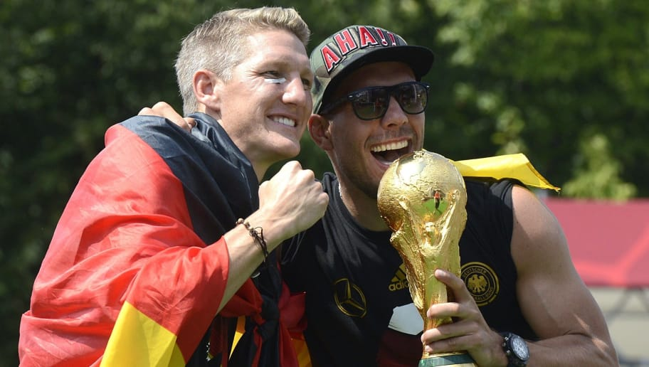 Germany's national footbal team midfielder Lukas Podolski (R) and Germany's midfielder Bastian Schweinsteiger cheer during celebrations of the German national team at Berlin's landmark Brandenburg Gate to celebrate their FIFA World Cup title on July 15, 2014. Germany won their fourth World Cup title, after 1-0 win over Argentina on July 13, 2014 in Rio de Janeiro in the FIFA World Cup Brazil final game.   AFP PHOTO / CLEMENS BILAN        (Photo credit should read CLEMENS BILAN/AFP/Getty Images)