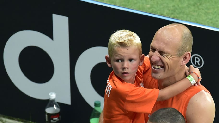 Netherlands' forward Arjen Robben celebrates holding his son after a quarter-final football match between Netherlands and Costa Rica at the Fonte Nova Arena in Salvador during the 2014 FIFA World Cup on July 5, 2014.   AFP PHOTO / GABRIEL BOUYS / AFP PHOTO / Gabriel BOUYS        (Photo credit should read GABRIEL BOUYS/AFP/Getty Images)