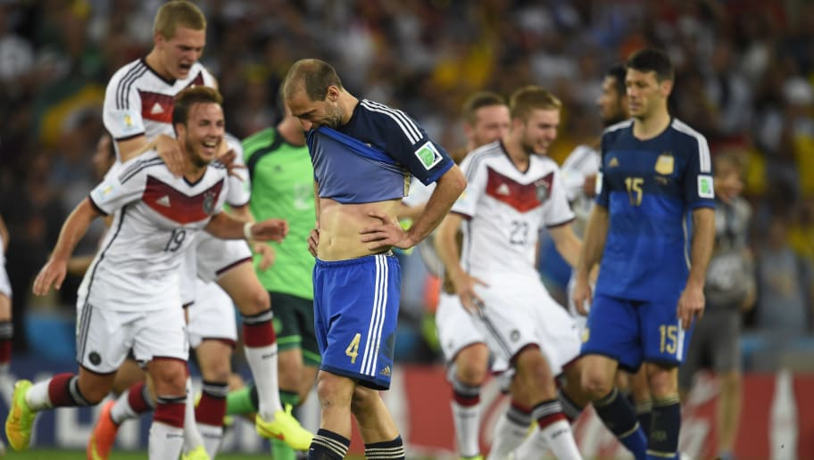 Germany's players celebrate as Argentina's defender Pablo Zabaleta reacts after losing the final football match between Germany and Argentina for the FIFA World Cup at The Maracana Stadium in Rio de Janeiro on July 13, 2014.    AFP PHOTO / ODD ANDERSEN        (Photo credit should read ODD ANDERSEN/AFP/Getty Images)