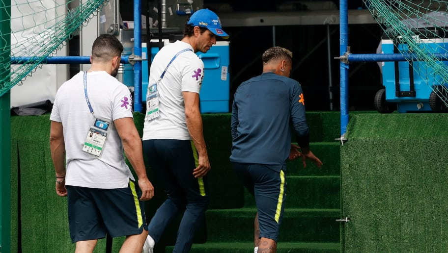 Brazil's forward Neymar (R) leaves the practice with team physio Bruno Mazziotti (L) and team Doctor  Rodrigo Lasmar (C) during a training session of Brazil national football team at Yug Sport Stadium, in Sochi, on June 19, 2018, ahead of the Russia 2018 World Cup football tournament. (Photo by Adrian DENNIS / AFP)        (Photo credit should read ADRIAN DENNIS/AFP/Getty Images)