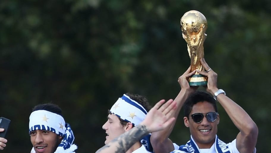 France's defender Raphael Varane (C) holds the trophy as he celebrates with teammates on the roof of a bus while parading down the Champs-Elysee avenue in Paris, on July 16, 2018 after winning the Russia 2018 World Cup final football match. (Photo by Eric FEFERBERG / various sources / AFP)        (Photo credit should read ERIC FEFERBERG/AFP/Getty Images)