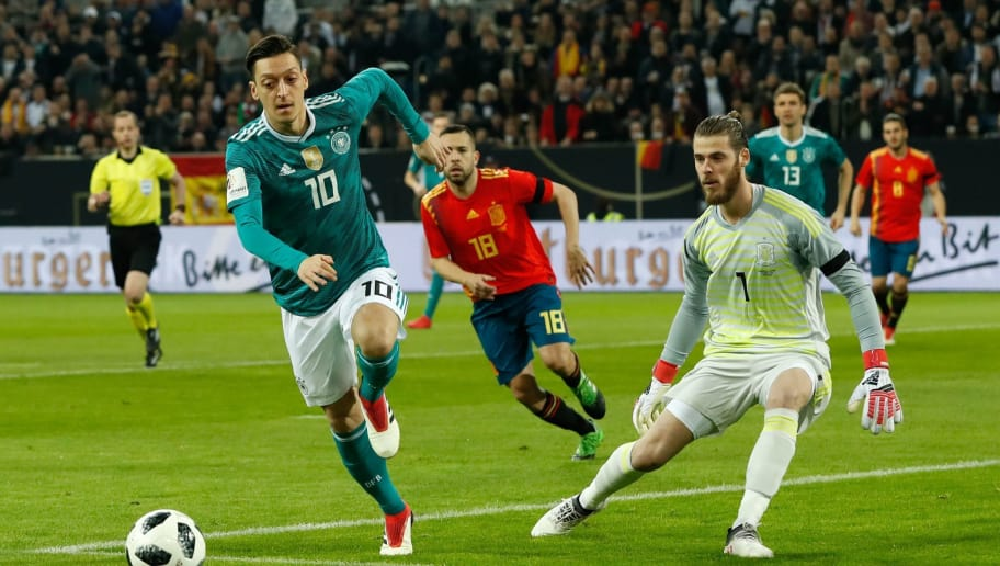Germany's midfielder Mesut Ozil (L) vies for the ball with Spain's goalkeeper David de Gea (R) during the international friendly football match of Germany vs Spain in Duesseldorf, western Germany, on March 23, 2018, in preparation of the 2018 Fifa World Cup. / AFP PHOTO / Odd ANDERSEN        (Photo credit should read ODD ANDERSEN/AFP/Getty Images)