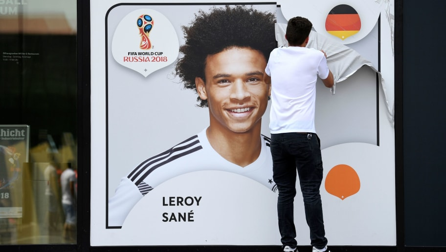 An employee removes a poster bearing a portrait of the German national player Leroy Sane from the facade of the Football Museum of the German Football Federation (DFB) on June 4, 2018 in Dortmund, western Germany, after the national coach Joachim Loew announced the final squad of the German national soccer team for the upcoming World Cup 2018 in Russia. - In a surprise omission, coach Joachim Loew left Manchester City striker Leroy Sane out of his 23-player list despite a strong season with the Premier League champions. (Photo by Federico Gambarini / dpa / AFP) / Germany OUT        (Photo credit should read FEDERICO GAMBARINI/AFP/Getty Images)
