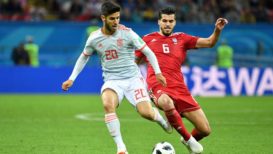 Spain's forward Marco Asensio (L) is marked by Iran's midfielder Saeid Ezatolahi during the Russia 2018 World Cup Group B football match between Iran and Spain at the Kazan Arena in Kazan on June 20, 2018. (Photo by SAEED KHAN / AFP) / RESTRICTED TO EDITORIAL USE - NO MOBILE PUSH ALERTS/DOWNLOADS        (Photo credit should read SAEED KHAN/AFP/Getty Images)