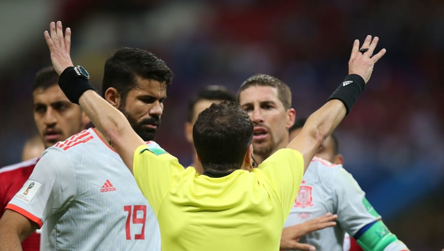 Uruguayan referee Andres Cunha speaks to Spain's defender Sergio Ramos (R) and forward Diego Costa (L) during the Russia 2018 World Cup Group B football match between Iran and Spain at the Kazan Arena in Kazan on June 20, 2018. (Photo by Roman Kruchinin / AFP) / RESTRICTED TO EDITORIAL USE - NO MOBILE PUSH ALERTS/DOWNLOADS        (Photo credit should read ROMAN KRUCHININ/AFP/Getty Images)
