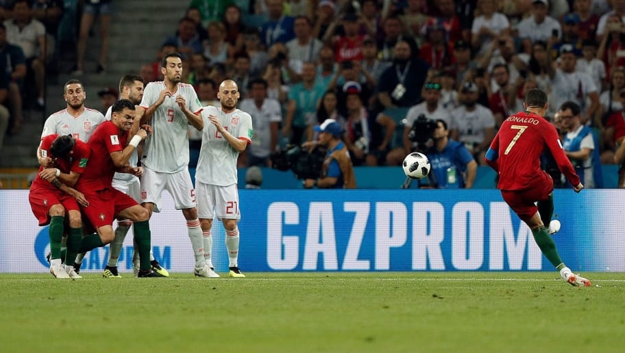 Portugal's forward Cristiano Ronaldo (R) shoots a free kick during the Russia 2018 World Cup Group B football match between Portugal and Spain at the Fisht Stadium in Sochi on June 15, 2018. (Photo by Adrian DENNIS / AFP) / RESTRICTED TO EDITORIAL USE - NO MOBILE PUSH ALERTS/DOWNLOADS        (Photo credit should read ADRIAN DENNIS/AFP/Getty Images)