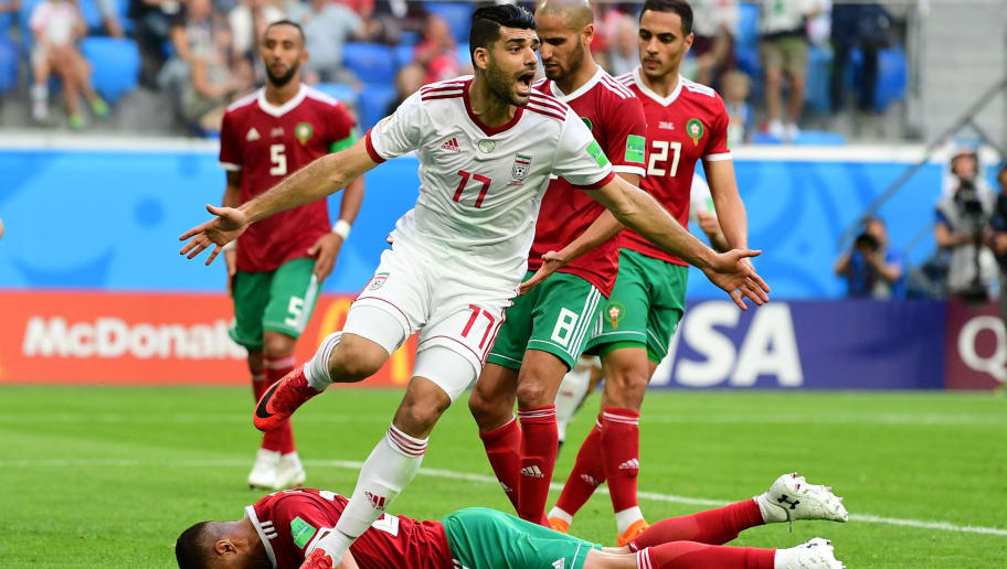 Morocco's forward Aziz Bouhaddouz (down) reacts after scoring an own goal as  Iran's forward Mehdi Taremi (up) celebrates during the Russia 2018 World Cup Group B football match between Morocco and Iran at the Saint Petersburg Stadium in Saint Petersburg on June 15, 2018. (Photo by Giuseppe CACACE / AFP) / RESTRICTED TO EDITORIAL USE - NO MOBILE PUSH ALERTS/DOWNLOADS        (Photo credit should read GIUSEPPE CACACE/AFP/Getty Images)