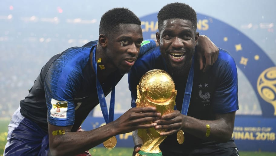 France's forward Ousmane Dembele (L) and France's defender Samuel Umtiti pose with the World Cup trophy after the Russia 2018 World Cup final football match between France and Croatia at the Luzhniki Stadium in Moscow on July 15, 2018. (Photo by FRANCK FIFE / AFP) / RESTRICTED TO EDITORIAL USE - NO MOBILE PUSH ALERTS/DOWNLOADS        (Photo credit should read FRANCK FIFE/AFP/Getty Images)