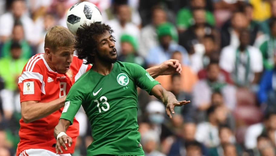 Russia's midfielder Yuri Gazinskiy (L) vies with Saudi Arabia's defender Yasser Al-Shahrani during the Russia 2018 World Cup Group A football match between Russia and Saudi Arabia at the Luzhniki Stadium in Moscow on June 14, 2018. (Photo by Kirill KUDRYAVTSEV / AFP) / RESTRICTED TO EDITORIAL USE - NO MOBILE PUSH ALERTS/DOWNLOADS        (Photo credit should read KIRILL KUDRYAVTSEV/AFP/Getty Images)