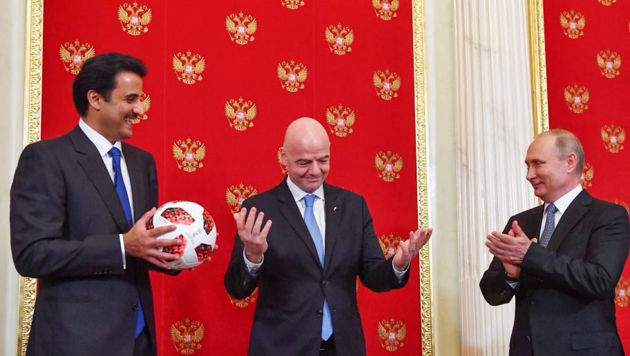 Emir of Qatar Sheikh Tamim bin Hamad Al-Thani (L) holds a ball as Russian President Vladimir Putin (R) and FIFA President Gianni Infantino (C) react during a symbolic transfer of the authority to Qatar to host the World Cup 2022 at the Kremlin in Moscow on July 15, 2018. (Photo by Yuri KADOBNOV / POOL / AFP)        (Photo credit should read YURI KADOBNOV/AFP/Getty Images)