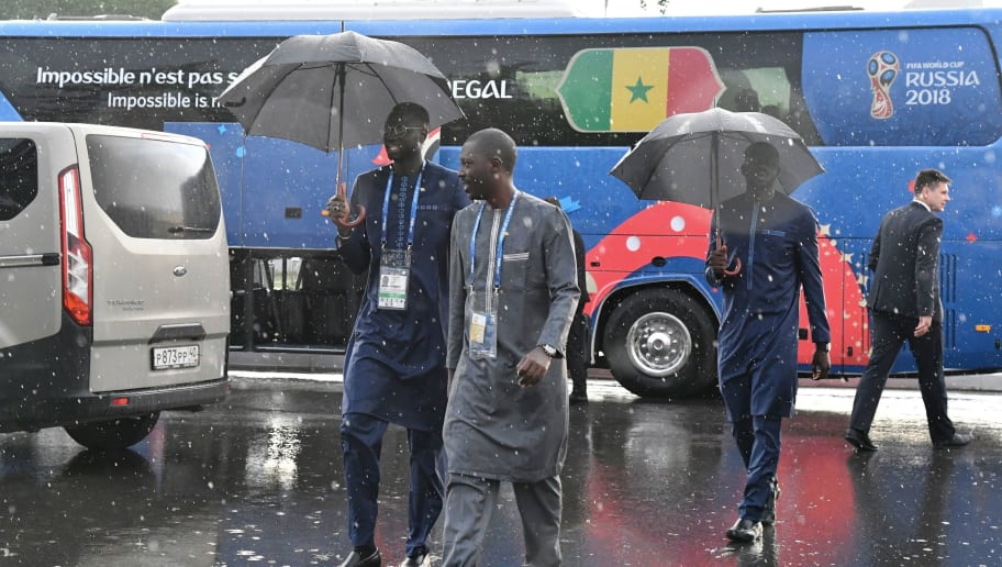 Senegal's captain Cheikhou Kouyate (L) walks next to the bus of Senegal's national football team as it rains upon the team's arrival in Kaluga on June 12, 2018, ahead of the Russia 2018 World Cup. (Photo by ISSOUF SANOGO / AFP)        (Photo credit should read ISSOUF SANOGO/AFP/Getty Images)