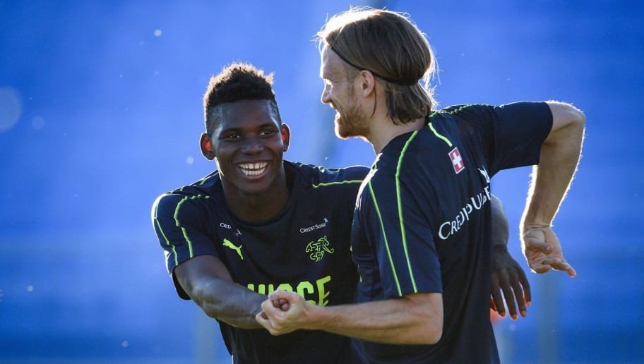 Switzerland's forward Breel Embolo (L) reacts with teammate defender Michael Lang during a training session on June 18, 2018 at Torpedo Stadium in Tolyatti also known as Togliatti, during the Russia 2018 World Cup football tournament. (Photo by Fabrice COFFRINI / AFP)        (Photo credit should read FABRICE COFFRINI/AFP/Getty Images)