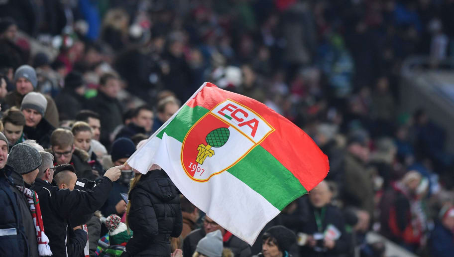 AUGSBURG, GERMANY - JANUARY 13: A supporter of Augsburg waves a flag during the Bundesliga match between FC Augsburg and Hamburger SV at WWK-Arena on January 13, 2018 in Augsburg, Germany. (Photo by Sebastian Widmann/Bongarts/Getty Images)