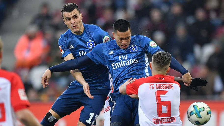 AUGSBURG, GERMANY - JANUARY 13: (L-R:) Filip Kostic of Hamburg, Bobby Wood of Hamburg and Jeffrey Gouweleeuw of Augsburg fight for the ball during the Bundesliga match between FC Augsburg and Hamburger SV at WWK-Arena on January 13, 2018 in Augsburg, Germany. (Photo by Sebastian Widmann/Bongarts/Getty Images)