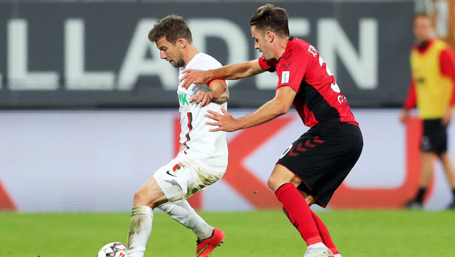 AUGSBURG, GERMANY - SEPTEMBER 30:  Daniel Baier of Augsburg is challanged by Christian Gunter of Freiburg during the Bundesliga match between FC Augsburg and Sport-Club Freiburg at WWK-Arena on September 30, 2018 in Augsburg, Germany.  (Photo by Christian Kaspar-Bartke/Bongarts/Getty Images)