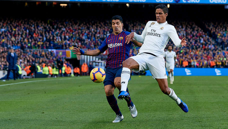 BARCELONA, SPAIN - OCTOBER 28: Raphael Varane (R) of Real Madrid CF competes for the ball with Luis Suarez of FC Barcelona during the La Liga match between FC Barcelona and Real Madrid CF at Camp Nou on October 28, 2018 in Barcelona, Spain. (Photo by David Aliaga/MB Media/Getty Images)