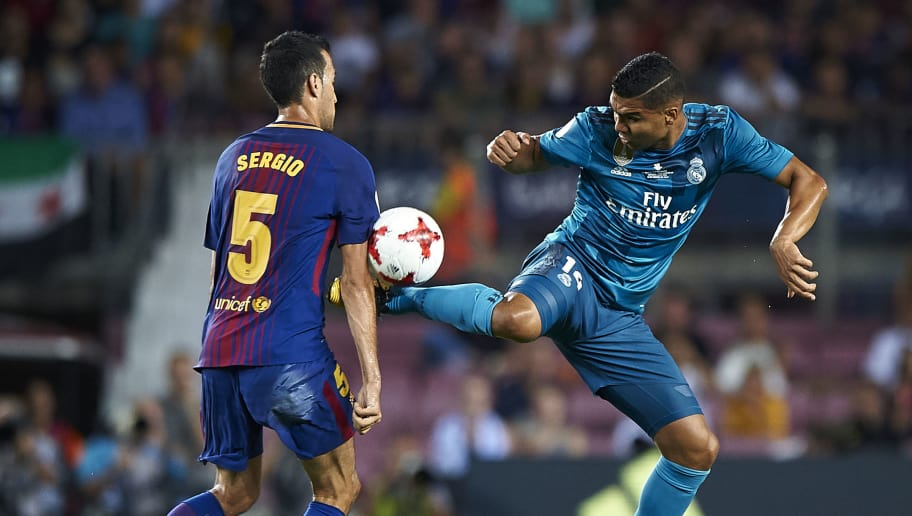 BARCELONA, SPAIN - AUGUST 13:  Sergio Busquets (L) of Barcelona competes for the ball with Casemiro of Real Madrid during the Supercopa de Espana Supercopa Final 1st Leg match between FC Barcelona and Real Madrid at Camp Nou on August 13, 2017 in Barcelona, Spain.  (Photo by fotopress/Getty Images)