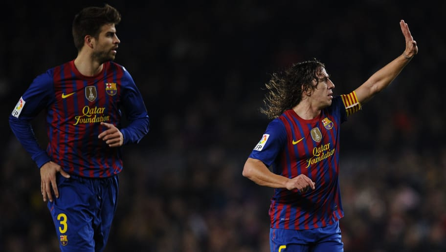 BARCELONA, SPAIN - FEBRUARY 19:  Carles Puyol of FC Barcelona (R) and his teammate Gerard Pique looks on during the La Liga match between FC Barcelona and Valencia CF at Camp Nou stadium on February 19, 2012 in Barcelona, Spain. Barcelona won 5-1.  (Photo by David Ramos/Getty Images)