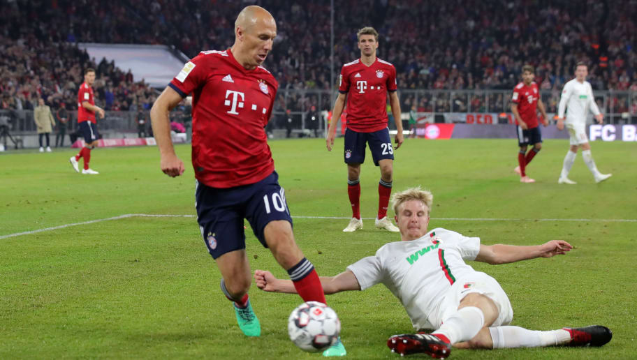 MUNICH, GERMANY - SEPTEMBER 25:  Arjen Robben of Bayern Munich is challanged by Martin Hinteregger of Augsburg during the Bundesliga match between FC Bayern Muenchen and FC Augsburg at Allianz Arena on September 25, 2018 in Munich, Germany.  (Photo by Alexander Hassenstein/Bongarts/Getty Images)