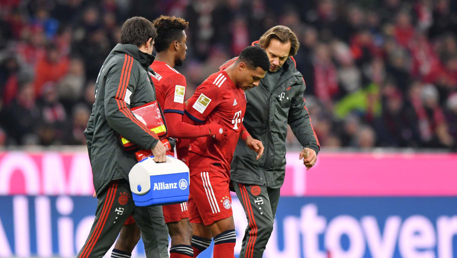 MUNICH, GERMANY - DECEMBER 19:  Serge Gnabry of Bayern Munich is helped off the pitch by medical staff during the Bundesliga match between FC Bayern Muenchen and RB Leipzig at Allianz Arena on December 19, 2018 in Munich, Germany.  (Photo by Sebastian Widmann/Bongarts/Getty Images)