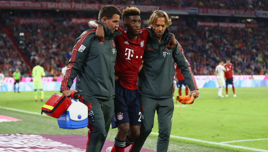 MUNICH, GERMANY - AUGUST 24:  An injured Kingsley Coman of Bayern Munich is given assistance during the Bundesliga match between FC Bayern Muenchen and TSG 1899 Hoffenheim at Allianz Arena on August 24, 2018 in Munich, Germany.  (Photo by Martin Rose/Bongarts/Getty Images)
