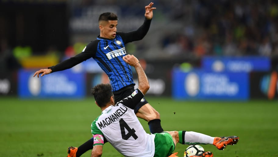 MILAN, ITALY - MAY 12:  Joao Cancelo (L) of FC Internazionale is tackled by Francesco Magnanelli of US Sassuolo during the Serie A match between FC Internazionale and US Sassuolo at Stadio Giuseppe Meazza on May 12, 2018 in Milan, Italy.  (Photo by Valerio Pennicino/Getty Images )