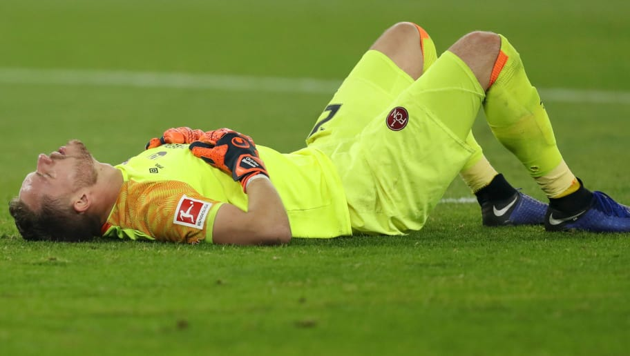 GELSENKIRCHEN, GERMANY - NOVEMBER 24:  Christian Mathenia of Nuernberg lies injured on the pitch during the Bundesliga match between FC Schalke 04 and 1. FC Nuernberg at Veltins-Arena on November 24, 2018 in Gelsenkirchen, Germany.  (Photo by Maja Hitij/Bongarts/Getty Images)