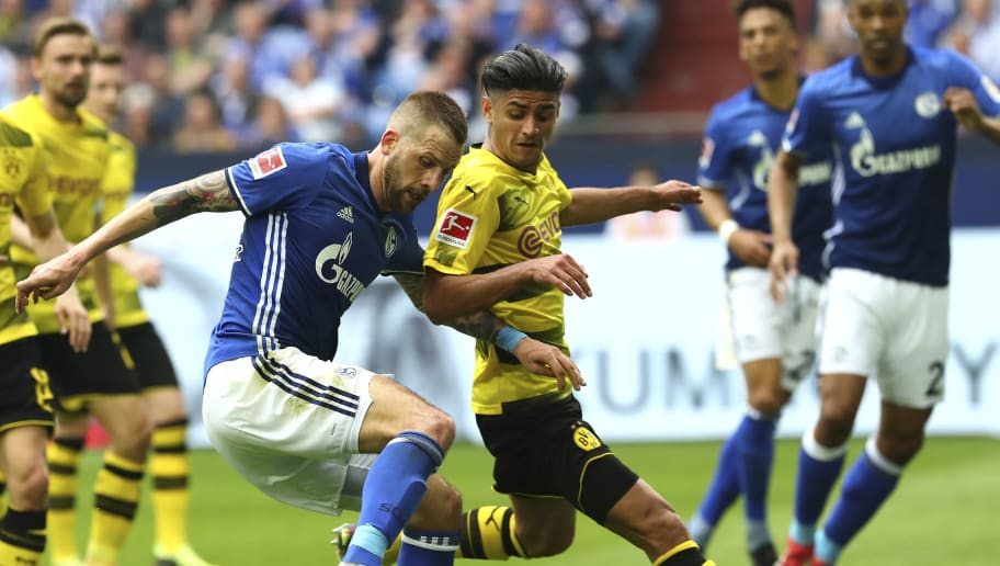 GELSENKIRCHEN, GERMANY - APRIL 15: Guido Burgstaller of Schalke and Mahmoud Dahoud of Dortmund battle for the ball during the Bundesliga match between FC Schalke 04 and Borussia Dortmund at Veltins-Arena on April 15, 2018 in Gelsenkirchen, Germany. (Photo by TF-Images/Getty Images)