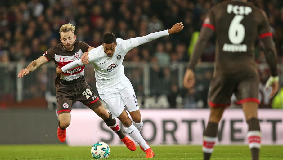 HAMBURG, GERMANY - OCTOBER 27: Jan-Marc Schneider of Pauli and Malcolm Cacutalua of Aue battle for the ball during the Second Bundesliga match between FC St. Pauli and FC Erzgebirge Aue at Millerntor Stadium on October 27, 2017 in Hamburg, Germany. (Photo by TF-Images/TF-Images via Getty Images)