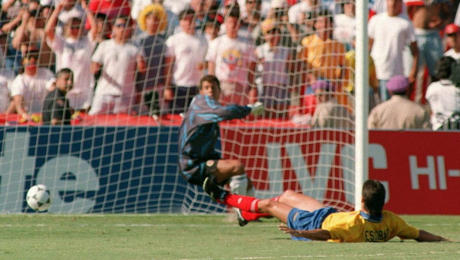 LOS ANGELES, UNITED STATES:  File photo dated 22 June 1994 shows Colombia defender Andres Escobar (R) laying on the pitch as he deflects a shot by John Harkes of the US into his own goal during their 94 World Cup match at the Rosa Bowl. A minute of silence will be held 15 June before the 1998 World Cup match opposing Colombia to Romania in memory of Escobar who was shot in 1994. (Photo credit should read ROMEO GACAD/AFP/Getty Images)