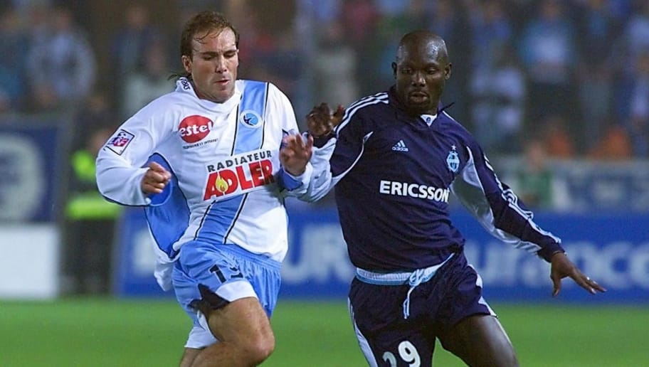 l'attaquant marseillais Georges Weah (D) est à la lutte avec le Strasbourgeois Luis Belloso, le 28 octobre 2000 au stade de la Meineau à Strasbourg, lors de la rencontre Strasbourg/Marseille comptant pour la 28e journée du championnat de France de football D1. AFP PHOTO FRANCK FIFE. (Photo by Franck FIFE / AFP)        (Photo credit should read FRANCK FIFE/AFP/Getty Images)