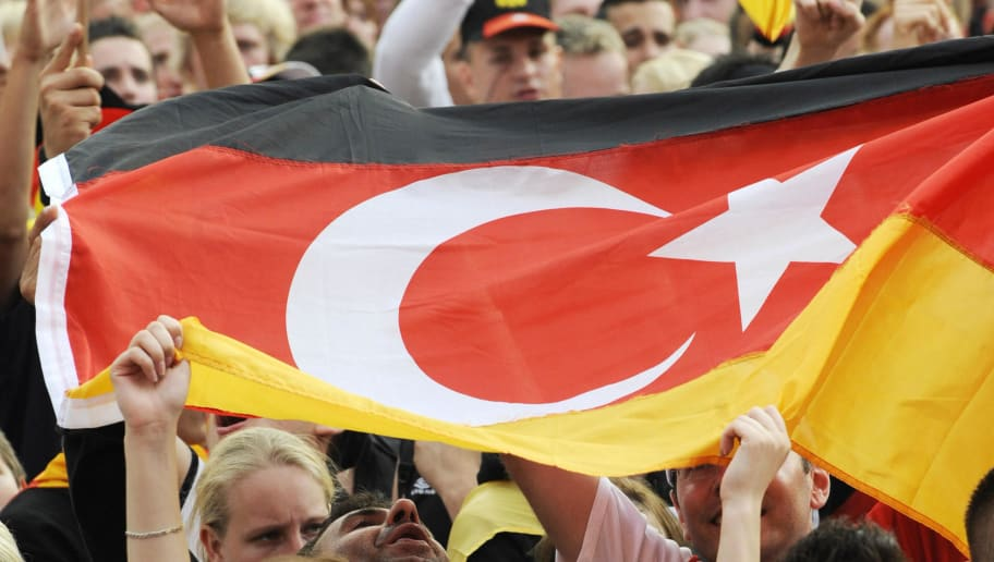 Football fans hold a German-Turkish flag