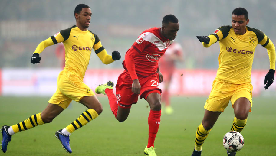 DUESSELDORF, GERMANY - DECEMBER 18:  Dodi Lukebakio of Fortuna Duesseldorf runs with the ball under pressure from Abdou Diallo of Borussia Dortmund and Manuel Akanji of Borussia Dortmund during the Bundesliga match between Fortuna Duesseldorf and Borussia Dortmund at Esprit-Arena on December 18, 2018 in Duesseldorf, Germany.  (Photo by Dean Mouhtaropoulos/Bongarts/Getty Images)