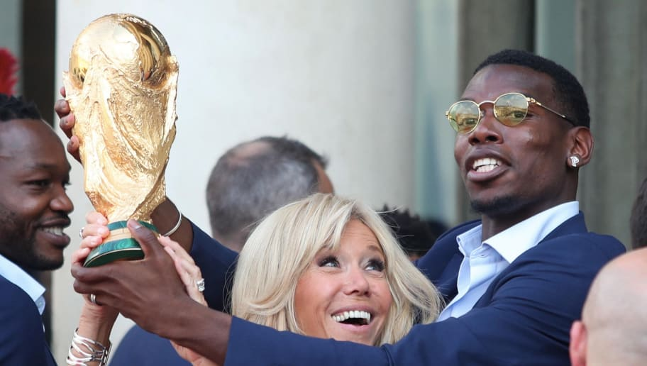 PARIS, FRANCE - JULY 16: Brigitte Macron and Paul Pogba hold up the World Cup trophy at a reception for France's national football team at Elysee Palace on July 16, 2018 in Paris, France. France beat Croatia 4-2 to win the 2018 FIFA World Cup last night at Moscow's Luzhniki Stadium. (Photo by Xavier Laine/Getty Images)