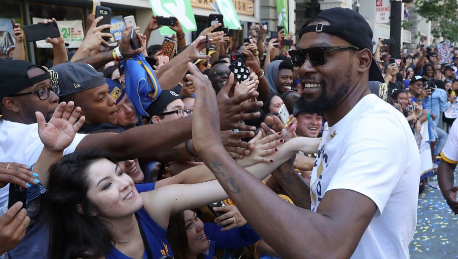 OAKLAND, CA - JUNE 12:  Kevin Durant #35 of the Golden State Warriors greets fans as he celebrates during the Golden State Warriors Victory Parade on June 12, 2018 in Oakland, California. The Golden State Warriors beat the Cleveland Cavaliers 4-0 to win the 2018 NBA Finals. NOTE TO USER: User expressly acknowledges and agrees that, by downloading and/or using this photograph, user is consenting to the terms and conditions of the Getty Images License Agreement.  (Photo by Justin Sullivan/Getty Images)