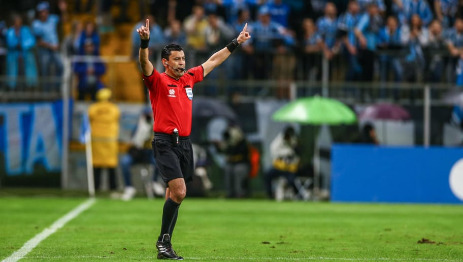 PORTO ALEGRE, BRAZIL - OCTOBER 02: Referee Roberto Tovar checks the Video Assistant Referee (VAR) before shows the red card to Luchetti of Atletico Tucuman during the match between Gremio and Atletico Tucuman, part of Copa Conmebol Libertadores 2018, at Arena do Gremio on October 02, 2018, in Porto Alegre, Brazil. (Photo by Lucas Uebel/Getty Images)