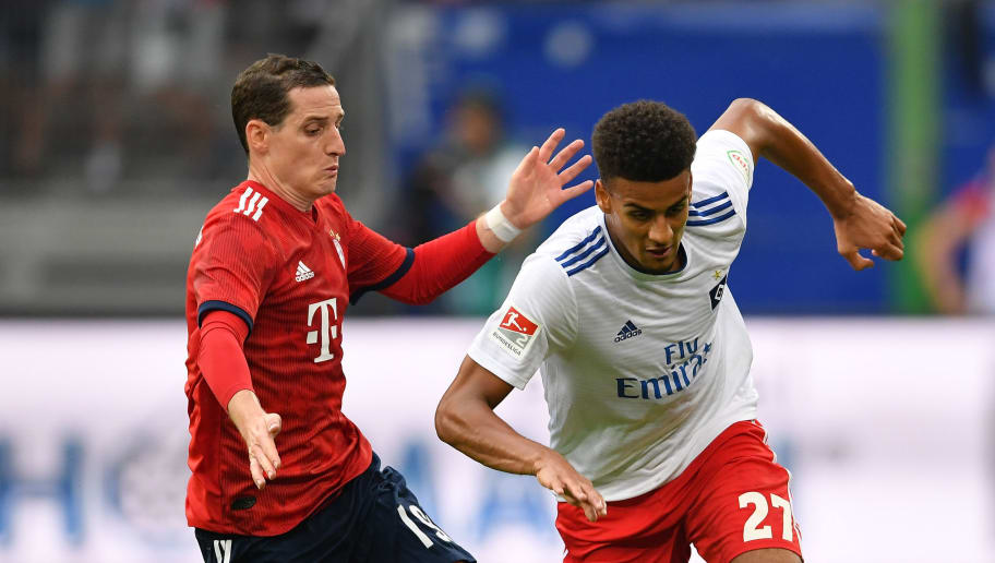 HAMBURG, GERMANY - AUGUST 15:  Josha Vagnoman of Hamburg is challenged by Sebastian Rudy of Muenchen during the friendly match between Hamburger SV and Bayern Muenchen at Volksparkstadion on August 15, 2018 in Hamburg, Germany.  (Photo by Stuart Franklin/Bongarts/Getty Images)