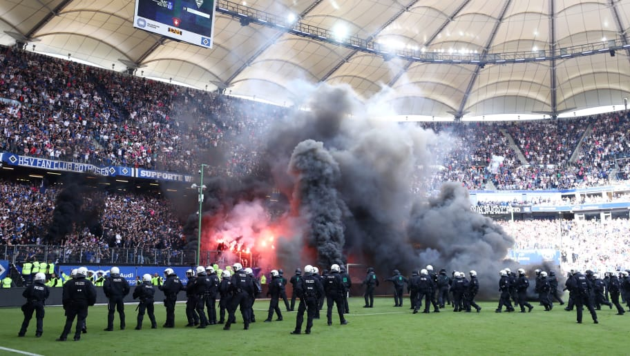 HAMBURG, GERMANY - MAY 12:  Police are seen as fans throw flares onto the pitch during the Bundesliga match between Hamburger SV and Borussia Moenchengladbach at Volksparkstadion on May 12, 2018 in Hamburg, Germany.  (Photo by Lars Baron/Bongarts/Getty Images)