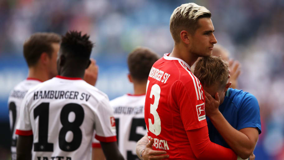 HAMBURG, GERMANY - MAY 12:  Julian Pollersbeck of Hamburger SV embraces Lewis Holtby of Hamburger SV as they react after their team is relegated after the Bundesliga match between Hamburger SV and Borussia Moenchengladbach at Volksparkstadion on May 12, 2018 in Hamburg, Germany.  (Photo by Lars Baron/Bongarts/Getty Images)