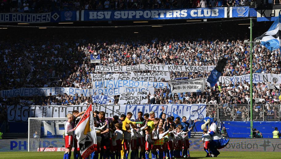HAMBURG, GERMANY - APRIL 21: Players of both team line up, as supporters of Hamburg display banners, before the Bundesliga match between Hamburger SV and Sport-Club Freiburg at Volksparkstadion on April 21, 2018 in Hamburg, Germany. (Photo by Stuart Franklin/Bongarts/Getty Images)