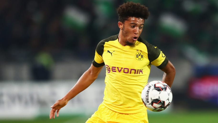 HANOVER, GERMANY - AUGUST 31:  Jadon Sancho of Borussia Dortmund is watched by Linton Maina of Hannover 96 during the Bundesliga match between Hannover 96 and Borussia Dortmund at HDI-Arena on August 31, 2018 in Hanover, Germany.  (Photo by Martin Rose/Bongarts/Getty Images)